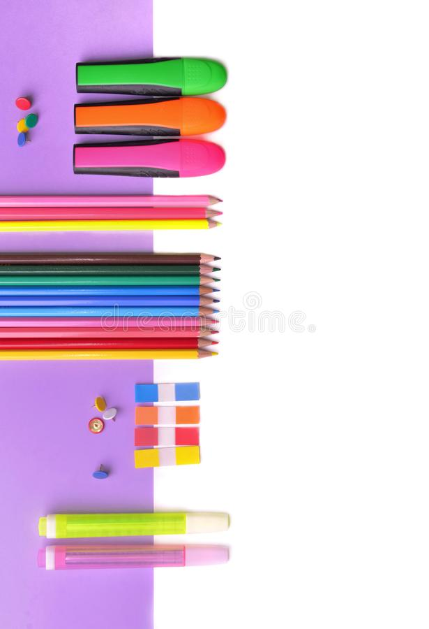 Lápis coloridos e penas de néon no papel malva e no branco foto de stock