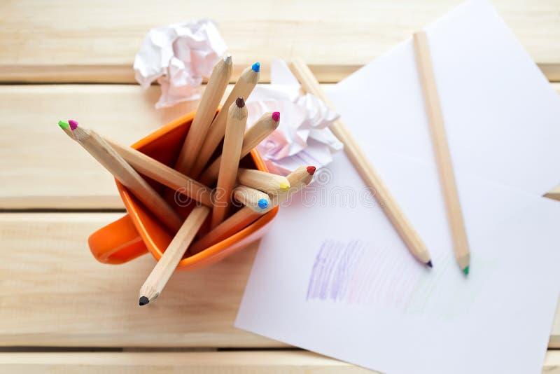 Lápis coloridos em uma caneca e em um papel amarrotado fotografia de stock royalty free