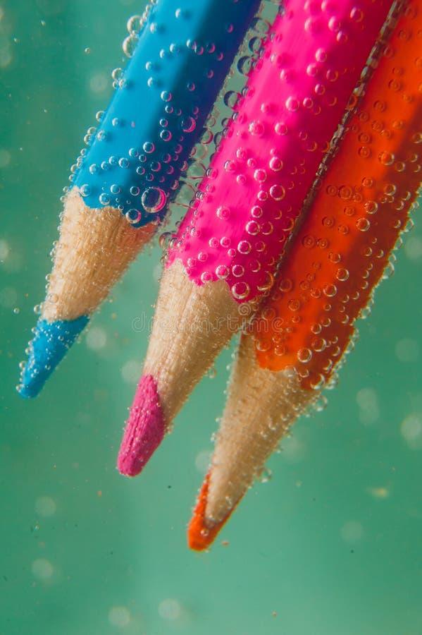 Lápis coloridos na água com bolhas fotos de stock