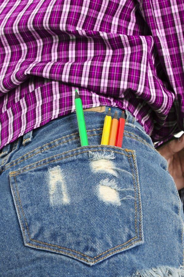 Lápis coloridos no bolso traseiro de calças azuis de brim dos girl's fotos de stock royalty free