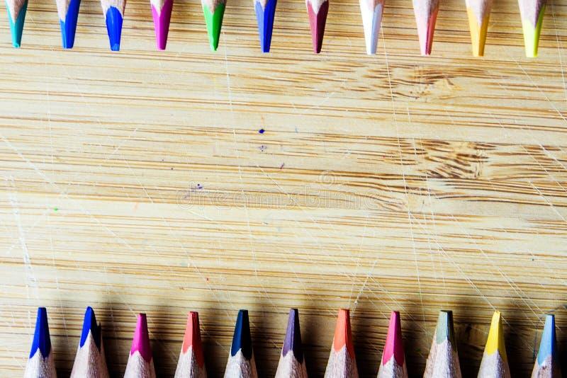 Lápis coloridos no fundo de madeira que forma um teste padrão com imagens de stock