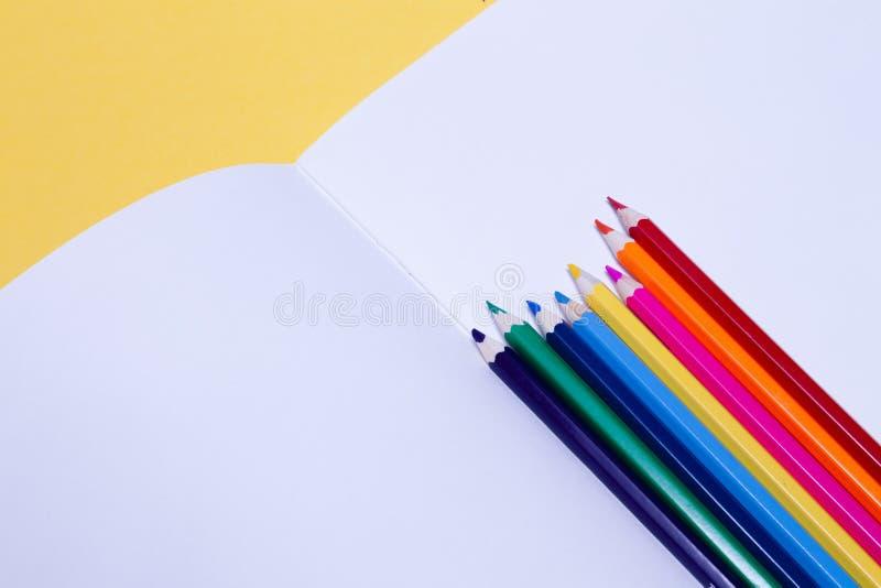 Lápis coloridos sem emenda do arco-íris em folhas do álbum do desenho da escola do Livro Branco no fundo amarelo isolado Conceito fotos de stock royalty free