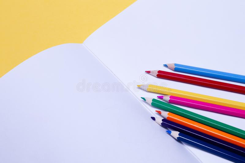 Lápis coloridos sem emenda do arco-íris em folhas do álbum do desenho da escola do Livro Branco no fundo amarelo isolado Conceito imagem de stock