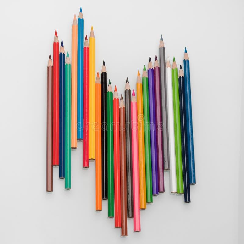 Lápis coloridos sob a forma de uma onda em uma opinião superior do fundo branco imagens de stock