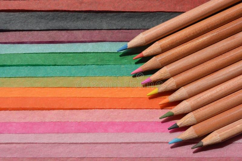 Lápis colorindo em um fundo de papel multicoloured fotos de stock royalty free