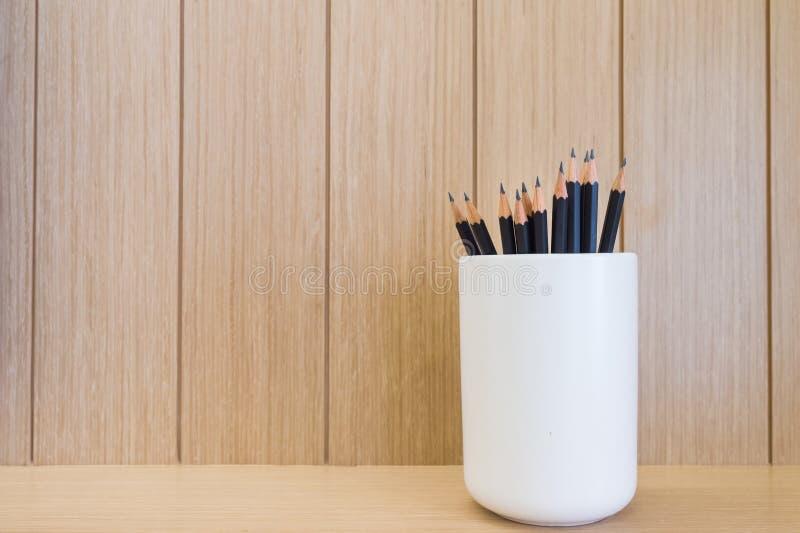 Lápis com fundo marrom de madeira da textura da caixa imagem de stock royalty free
