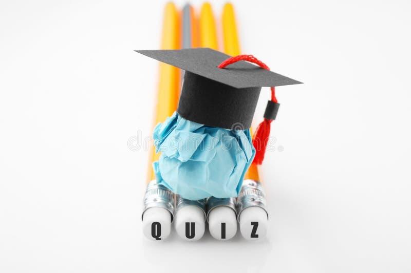 Lápis com inscrição do QUESTIONÁRIO Figura de papel da educa??o com tamp?o da gradua??o imagem de stock