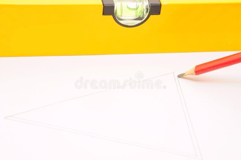 Lápis com um nível de espírito do laser imagem de stock