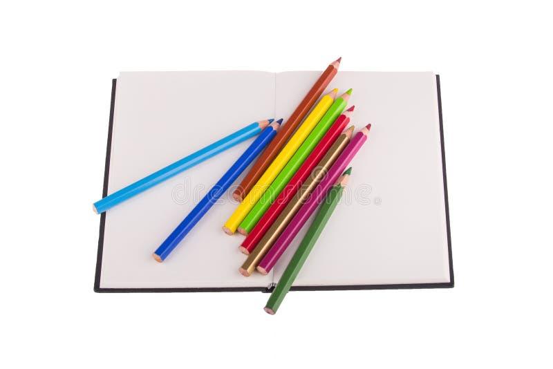 Lápis da cor colocados no caderno imagem de stock
