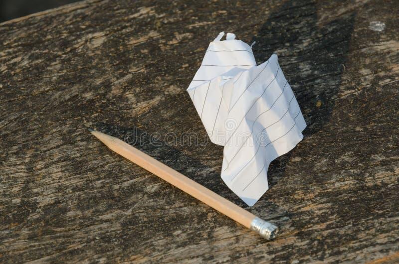 Lápis de papel e usado amarrotado no fundo de madeira foto de stock