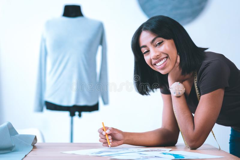 Lápis de sorriso da terra arrendada da menina em costurar a oficina imagens de stock