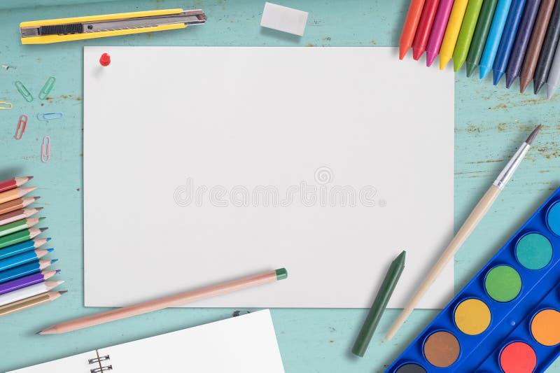 L?pis do papel vazio e da cor, past?is, paleta da pintura da aquarela da pena da cor na tabela de madeira azul imagem de stock royalty free
