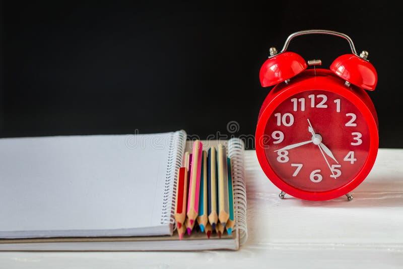 L?pis e cadernos coloridos em uma tabela com o despertador Fontes da escola e de escrit?rio Front View fotografia de stock