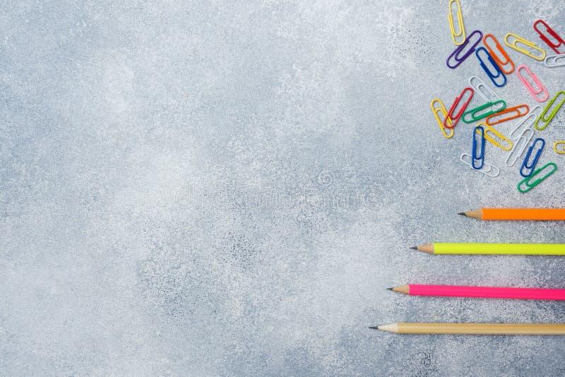 Lápis e clipes de papel coloridos brilhantes na tabela cinzenta o conceito da escola fotos de stock