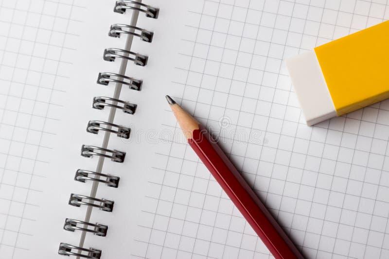 Lápis e eliminador do bloco de notas imagem de stock