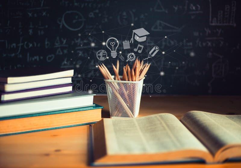 Lápis e livros abertos com fórmulas no quadro Conceito da instrução fotografia de stock royalty free