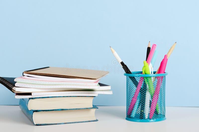 lápis Multi-coloridos, penas em um suporte e livros com cadernos em uma tabela branca em um fundo azul, local de trabalho do escr fotografia de stock