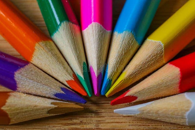 Lápis multicoloridos que formam um meio círculo da cor isolado no fundo de madeira imagem de stock royalty free