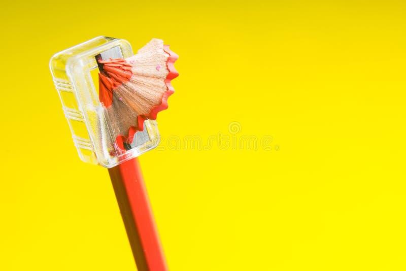 Lápis vermelho apontado no fundo amarelo fotografia de stock