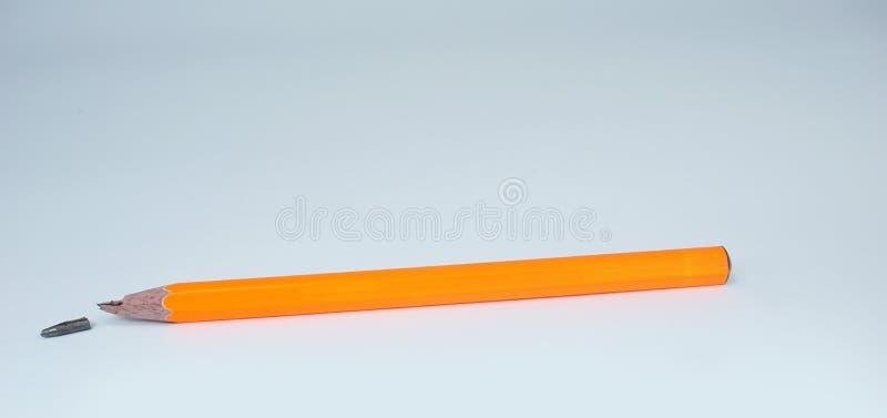 Lápiz anaranjado quebrado en el fondo blanco imagen de archivo libre de regalías