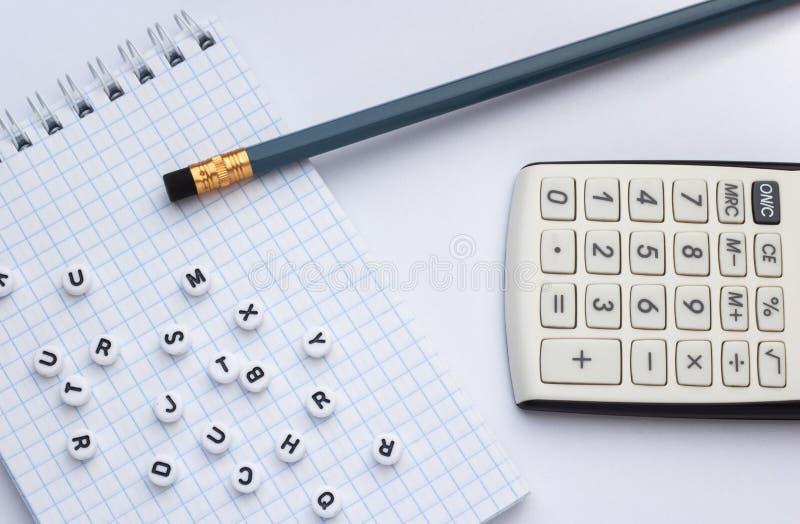 Lápiz, calculadora y cuaderno con las letras en el fondo blanco fotos de archivo libres de regalías