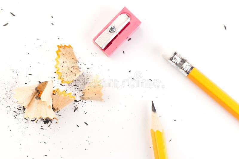 Lápiz de madera aislado en un fondo blanco con las virutas y los sacapuntas de lápiz fotografía de archivo