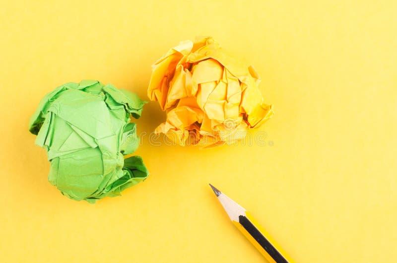 Lápiz de madera del grafito y arrugar el fondo amarillo del lkon del papel imagenes de archivo