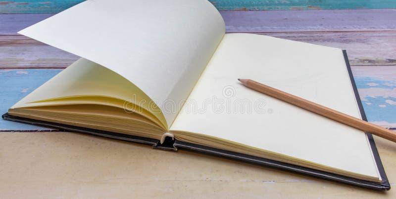 Lápiz de madera marrón sobre un cuaderno colocado en un antiguo escritorio de madera en tonos pastel y fondo negro fotos de archivo libres de regalías