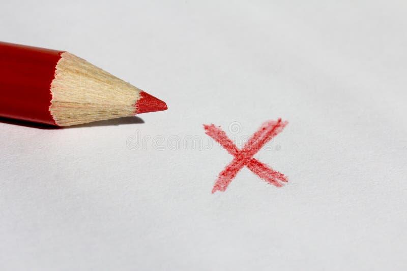 Lápiz del color rojo y marca de X foto de archivo