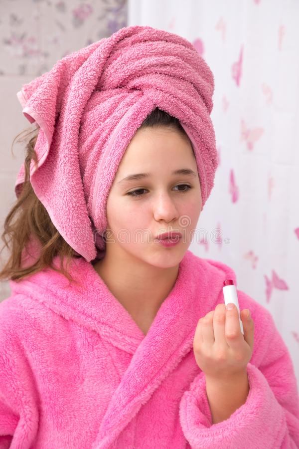 Lápiz labial divertido del uso de la chica joven para su cara en el cuarto de baño fotografía de archivo
