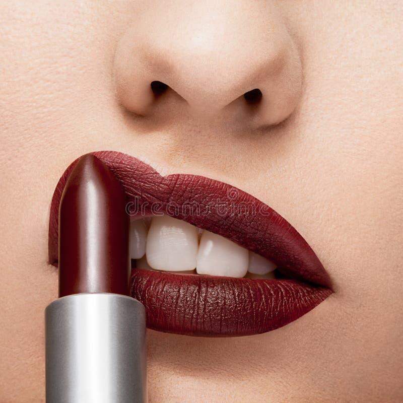 Lápiz labial rojo que consigue aplicado en los labios fotos de archivo