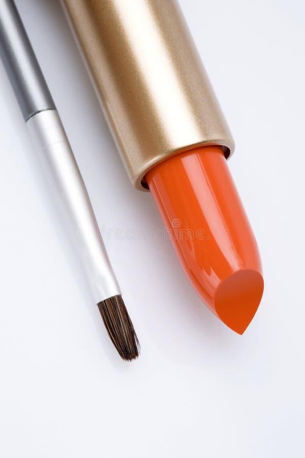 Lápiz labial y cepillo del maquillaje fotos de archivo
