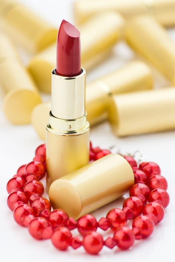 Lápiz labial y joyería rojos imagen de archivo
