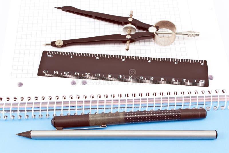 Lápiz, pluma, compás de dibujo y regla de madera en el cuaderno espiral foto de archivo libre de regalías