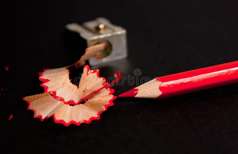Lápiz rojo con las virutas del lápiz y de lápiz de los sacapuntas cierre para arriba imagen de archivo