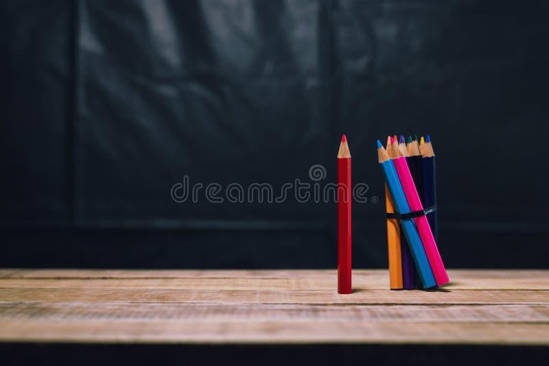 Lápiz rojo del grupo del color en la tabla de madera imagen de archivo