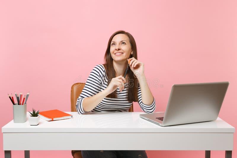 Lápiz sonriente joven de la tenencia de la mujer que mira el sueño para arriba de pensamiento para sentar el trabajo el escritori foto de archivo