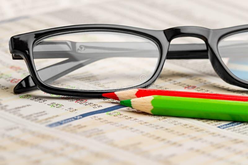 Lápiz verde rojo de la pluma de los vidrios en el periódico con el fondo del concepto del negocio de las finanzas de la carta de  fotos de archivo libres de regalías