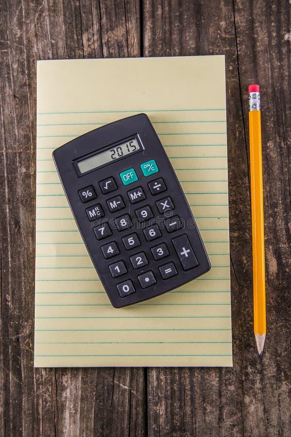 Lápiz y calculadora amarillos de la tableta en el escritorio del vintage fotos de archivo
