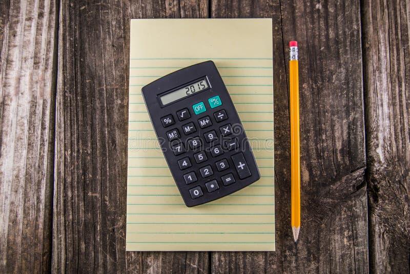 Lápiz y calculadora amarillos de la tableta en el escritorio del vintage imagen de archivo