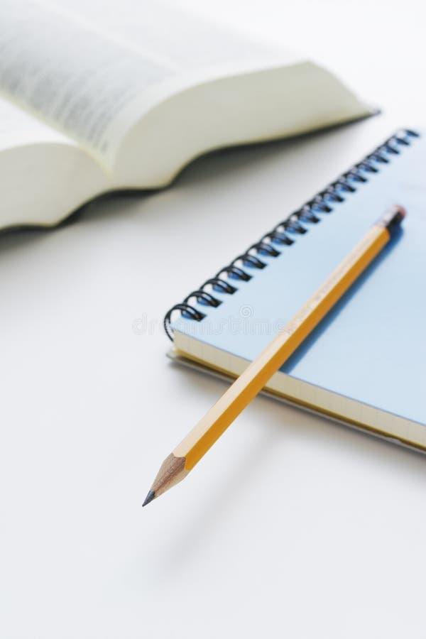 Lápiz y cuaderno y diccionario en el escritorio fotografía de archivo