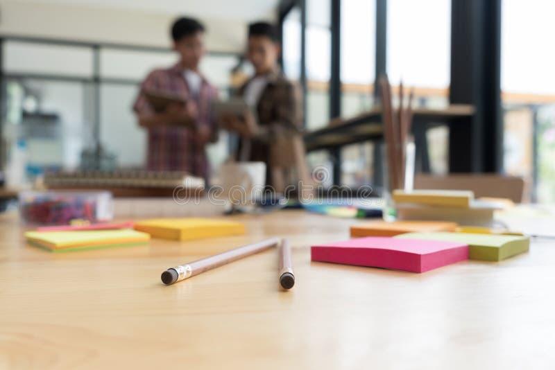 lápiz y nota pegajosa sobre la tabla con el fondo de univers jovenes imagen de archivo