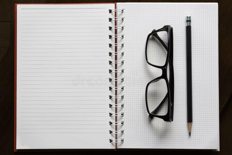 Lápiz y vidrios en el libro abierto con la línea en la madera marrón fotografía de archivo