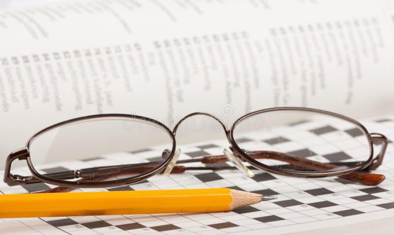 Lápiz y vidrios en un crucigrama fotografía de archivo libre de regalías