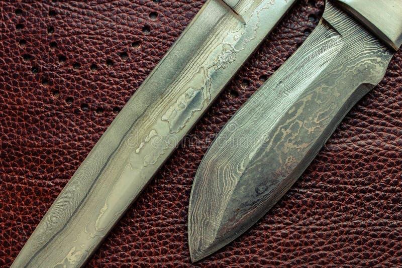 Lâminas de aço de Damasco Knifes da caça Fundo de Brown fotografia de stock