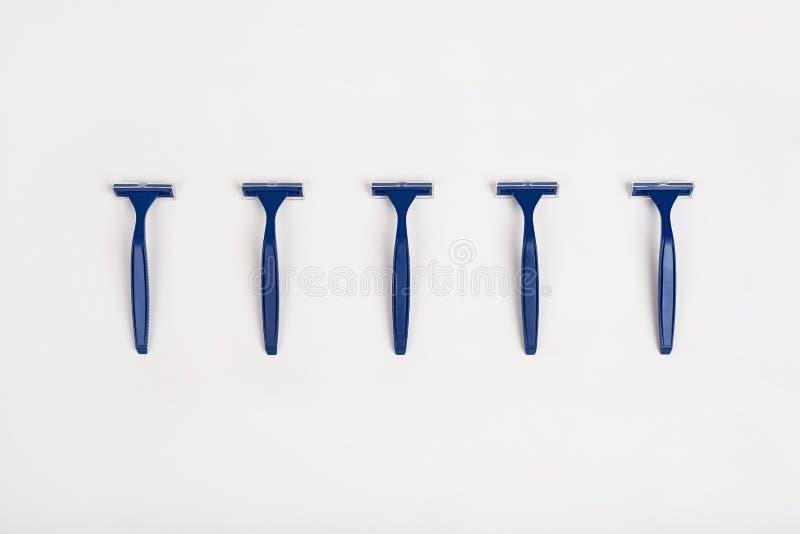 Lâminas unisex azuis no fundo branco Conceito do cuidado do corpo da pele da higiene Remo??o do cabelo Estilo m?nimo Configura??o fotografia de stock