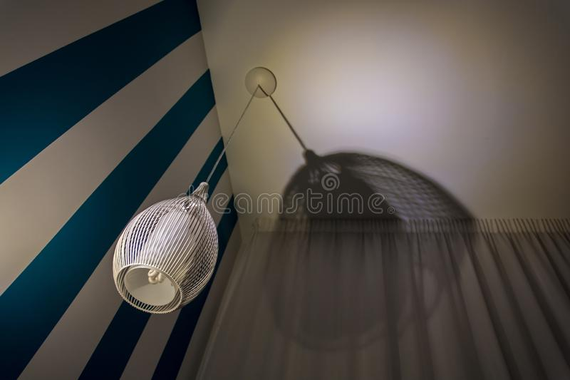 Lâmpada à moda do teto ao lado da parede branca azul com cortina fotos de stock royalty free