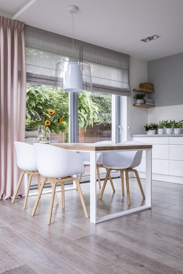 A lâmpada acima da tabela de madeira e das cadeiras brancas no interior da sala de jantar com drapeja e janela Foto real foto de stock