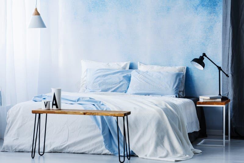 Lâmpada acima da tabela de madeira na frente da cama com a cobertura azul no pas imagens de stock