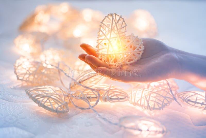 Lâmpada alaranjada pastel macia nas cestas de bambu na forma do coração na mão dois fotos de stock royalty free